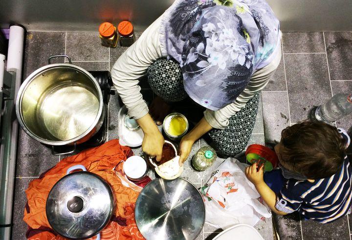 Bushracooks food for her family inside her temporary living quarters at Berlin'€™s Tempelhof refugee shelter.