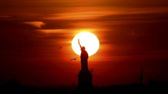 The sun sets behind the Statue of Liberty in New York's Harbor as seen from the Brooklyn borough of New York February 27, 2016. REUTERS/Brendan McDermid      TPX IMAGES OF THE DAY