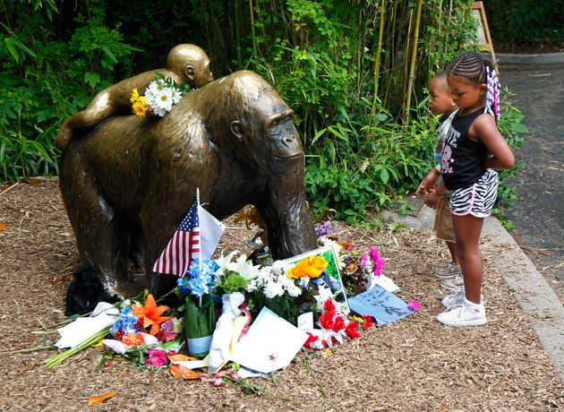 Tributes to Harambe around a bronze statue of a gorilla and her babyat the