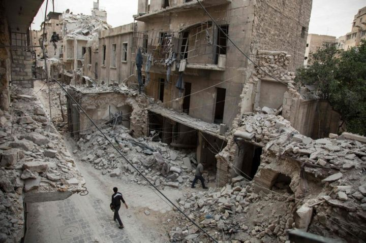 A man walks past destroyed buildings in a neighborhood of Aleppo, Syria, that was recently targeted by regime airstrikes.&nbs
