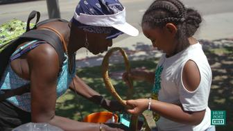 Khloe Thompson distributing one of her handmade bags to a homeless woman