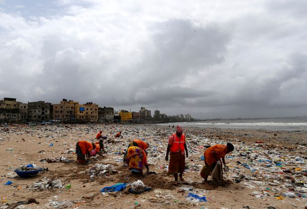 Municipal workers collect garbage as they clean a beach in Mumbai, India, on Aug. 14,