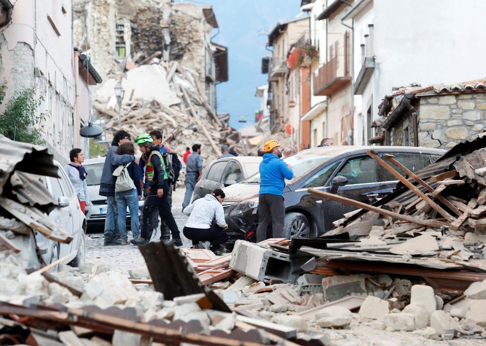 People stand amid the rubble after a quake hit Amatrice, Italy on August 24, 2016.