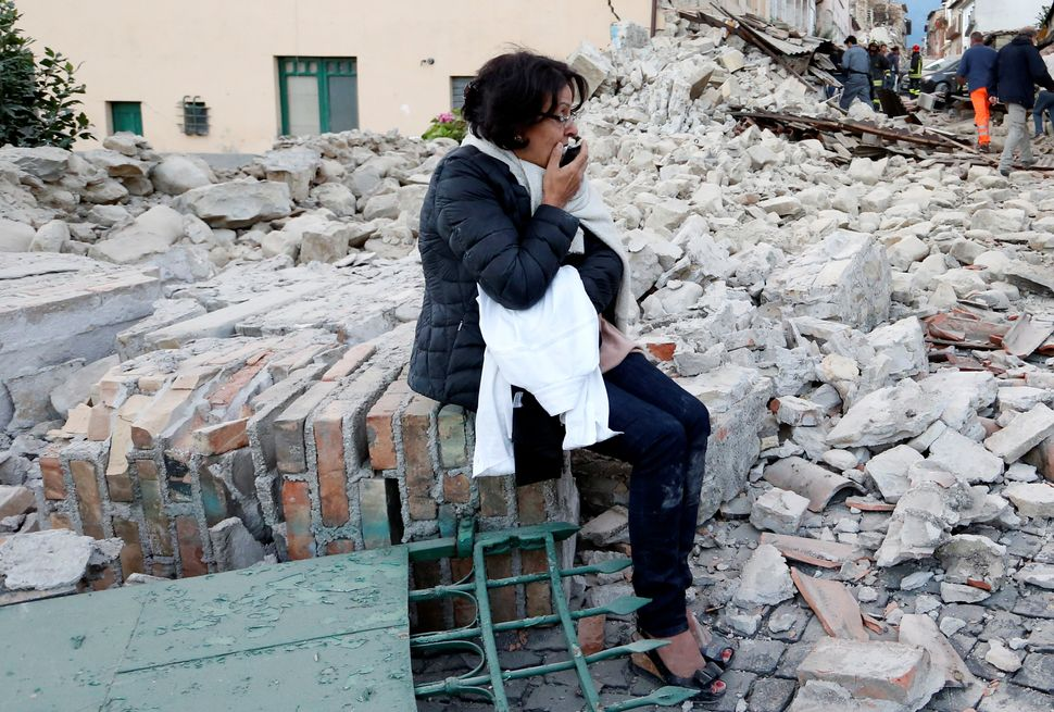 A woman sits amongst rubble following a quake in Amatrice, Italy, on Wednesday.