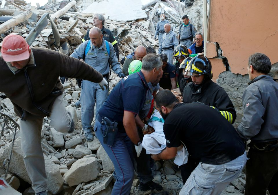Rescuers remove a quake victim from the rubble in Amatrice,