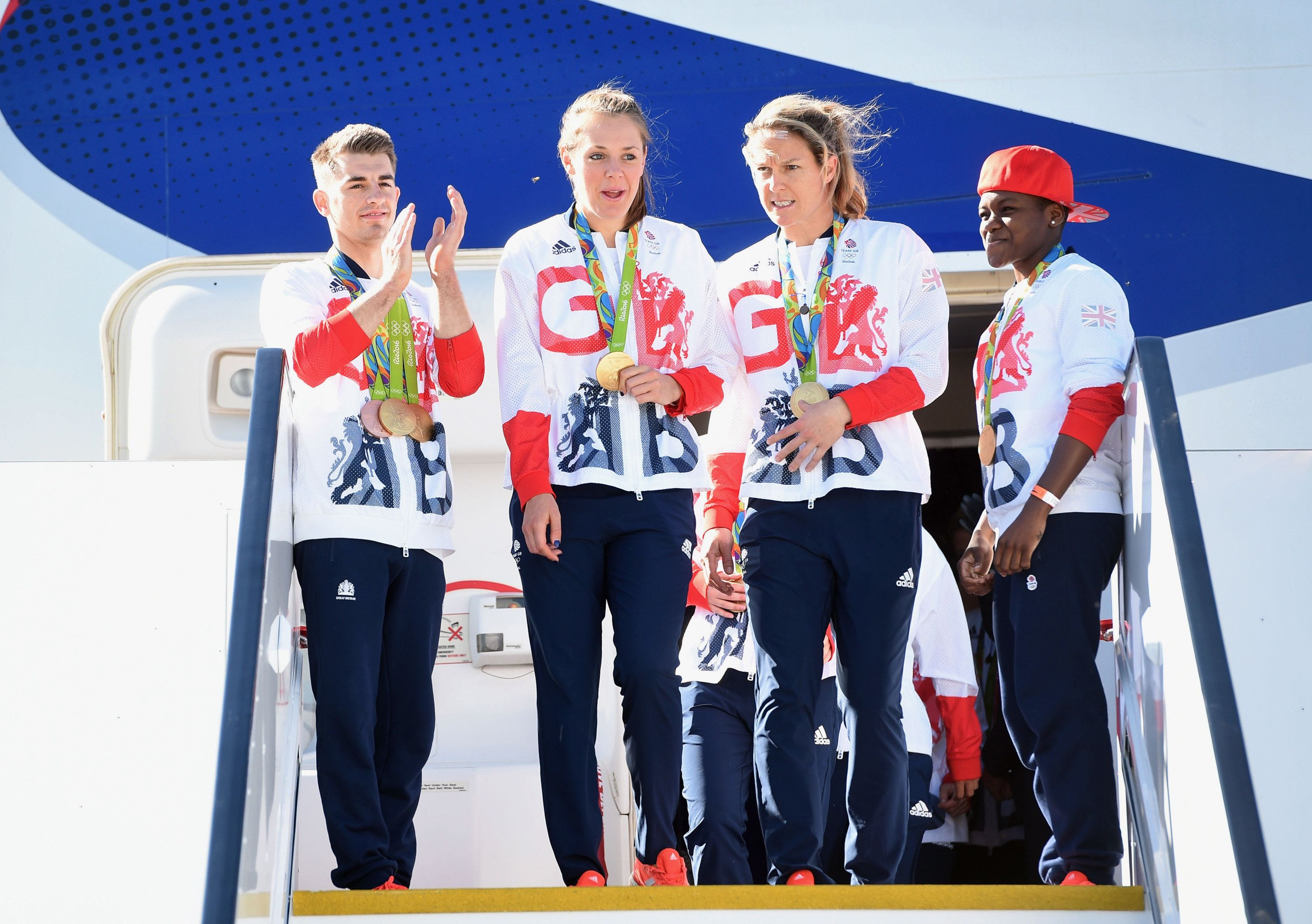 LONDON, ENGLAND - AUGUST 23:  Team GB Gymnast and gold medallist Max Whitlock (L) and gold medallist and boxer Nicola Adams (R) look on as members of the women's hockey team leave the plane after arriving home at Heathrow Airport on August 23, 2016 in London, England. The 2016 British Olympic Team arrived back to Heathrow on a British Airways flight today having finished second in the medal table at the Rio Olympics. They totalled 67 medals including 27 Gold and 23 Silver in Great Britain's strongest Olympic performance in over a century.  (Photo by Stuart C. Wilson/Getty Images)
