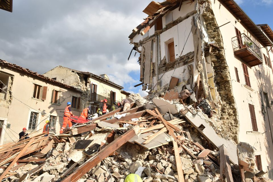 Rescuers clear debris while searching for victims in damaged buildings on Aug. 24 in Arquata del Tronto, Italy.