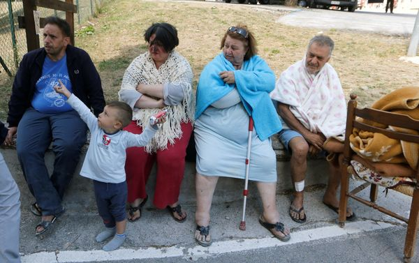 People sit along a road following an earthquake in Amatrice.