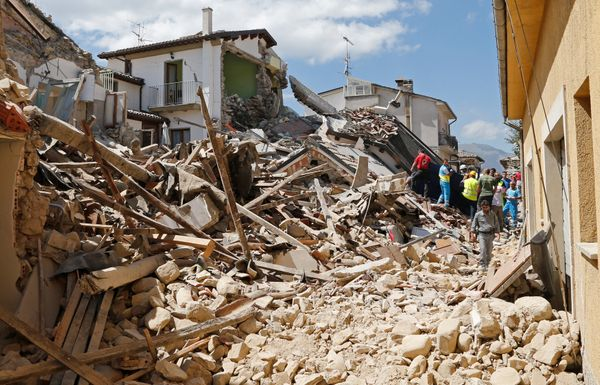 People and rescuers stand next collapsed buildings in Amatrice.