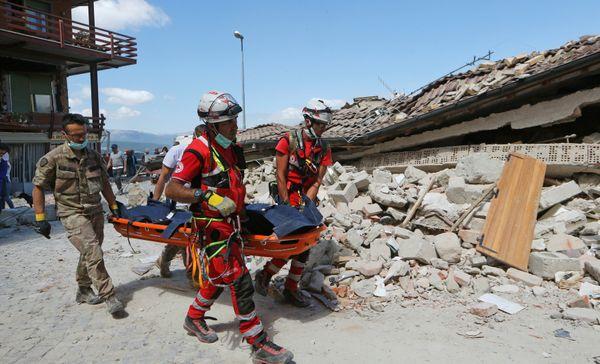 Rescuers carry a body awayin Amatrice.