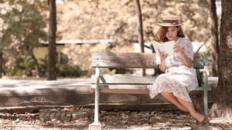 Vintage girl reading book in park