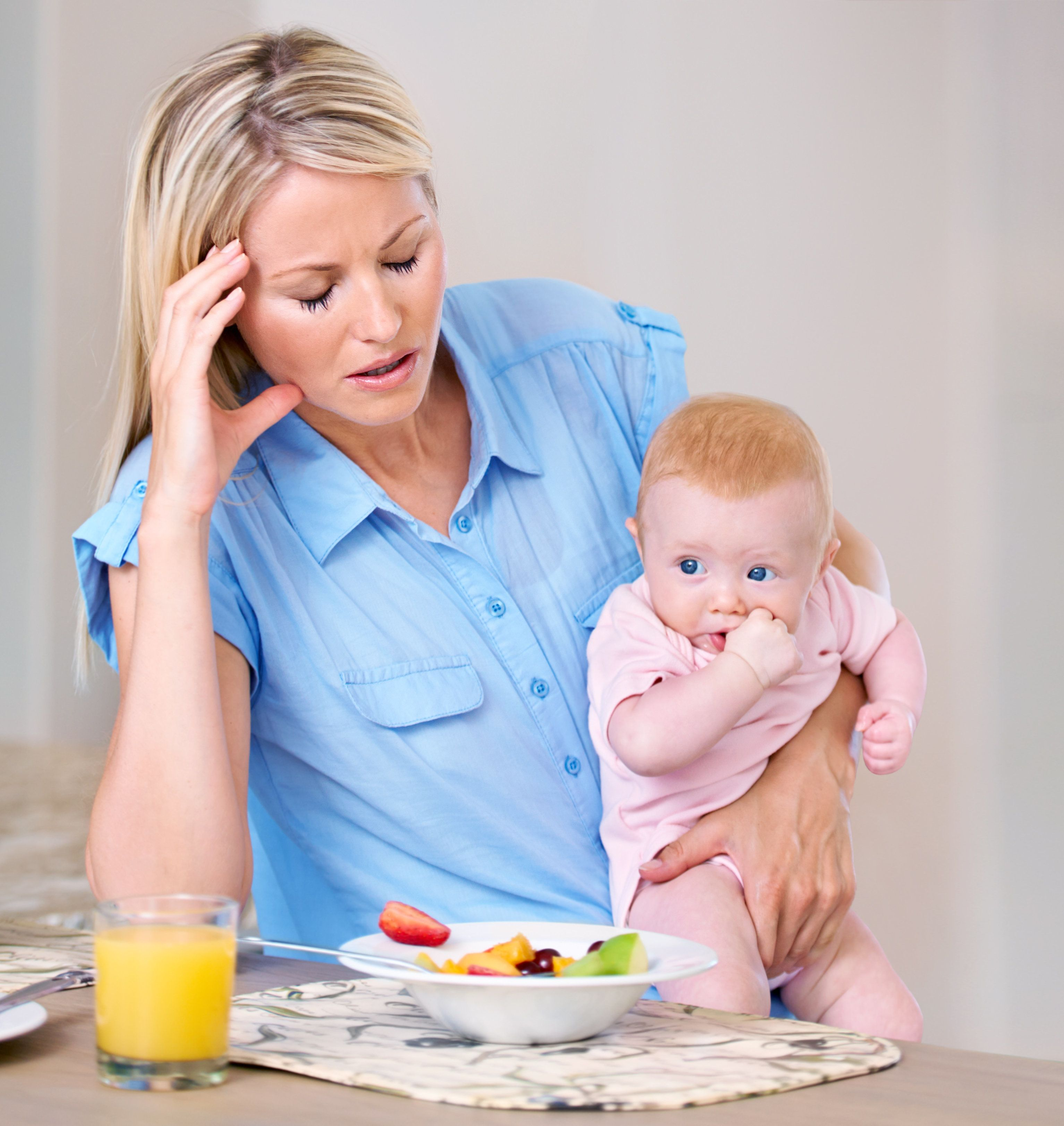 Young mother holding her baby at breakfast time looking tired