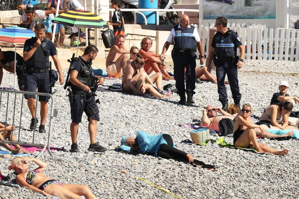 Police fine the first person for wearing a burkini on the Promenade des Anglais beach in Nice, France on August 23, 2016. The