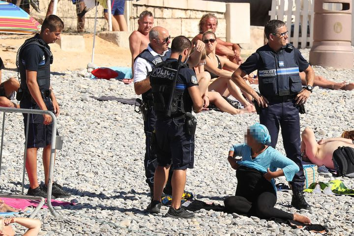 A woman was apprehended on the beach in Nice, France by four armed policemen.