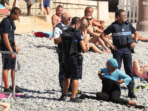 Police apprehend a woman on the beach for wearing body-covering swimwear on the Promenade des Anglais beach in Nice