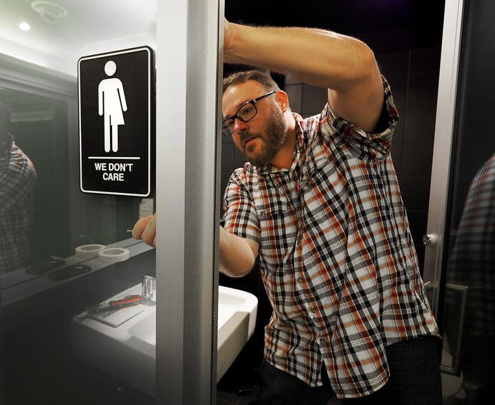 Museum Manager Jeff Bell puts up a gender neutral bathroom sign in the 21C Museum Hotel public restrooms on May 10, 2016