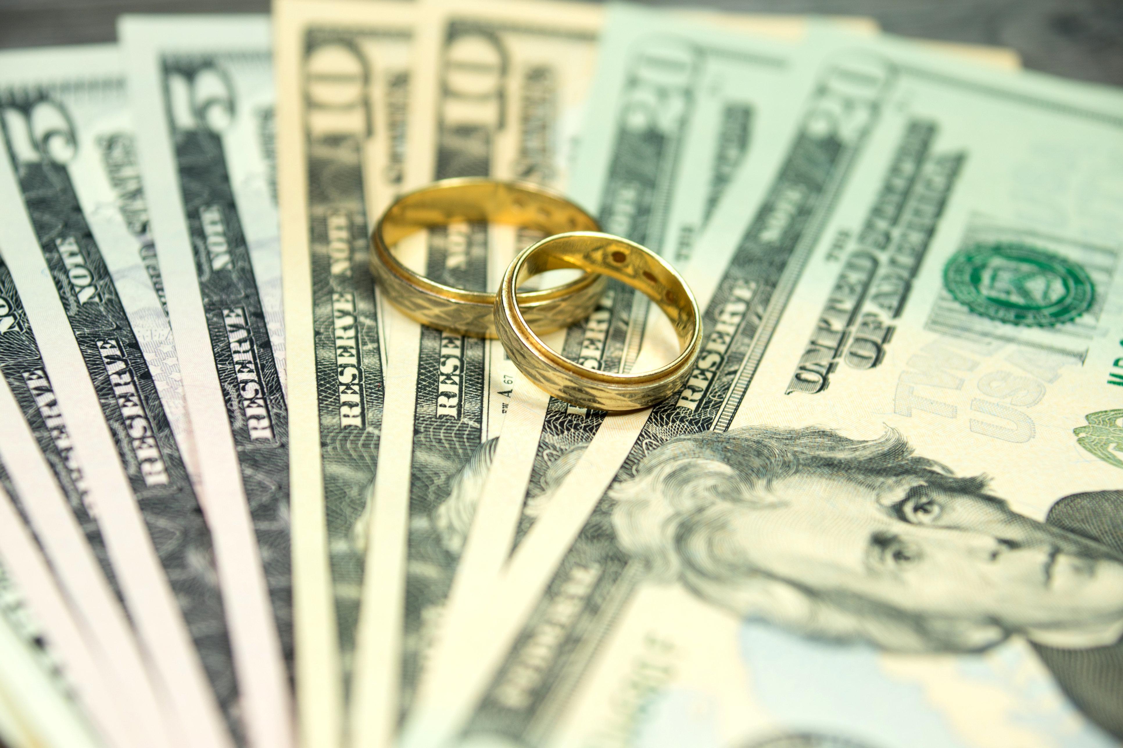 Zwei Eheringe und Geldscheine