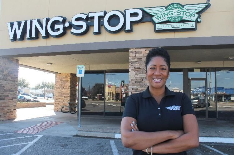 Howell poses in front of one of her Miami-based Wingstop franchises.