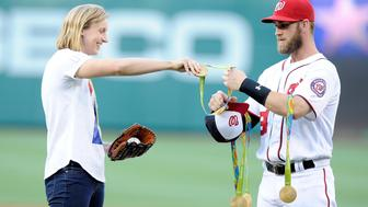 WASHINGTON, DC - AUGUST 24:  Katie Ledecky hands her Olympic medals to Bryce Harper #34 before throwing out the opening pitch before the game between the Baltimore Orioles and the Washington Nationals at Nationals Park on August 24, 2016 in Washington, DC.  (Photo by Greg Fiume/Getty Images)