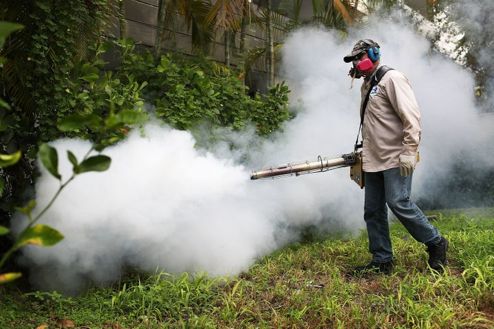Carlos Varas, a Miami-Dade County mosquito control inspector, uses a Golden Eagle blower to spray pesticide to kill mosquitos in the Miami Beach neighborhood.
