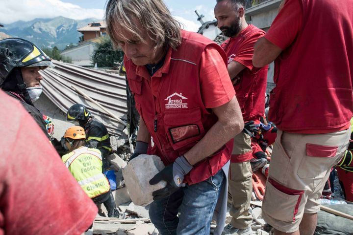 A volunteer helps rescuers search for victims in damaged buildings after a strong earthquake hit Amatrice on August 24, 2016.