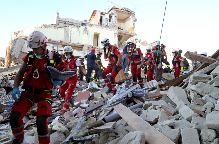 Rescuers walk through rubble following the earthquake in Amatrice, central Italy, August 24, 2016.