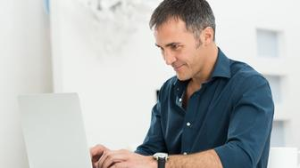 Portrait Of A Happy Mature Man Using Laptop