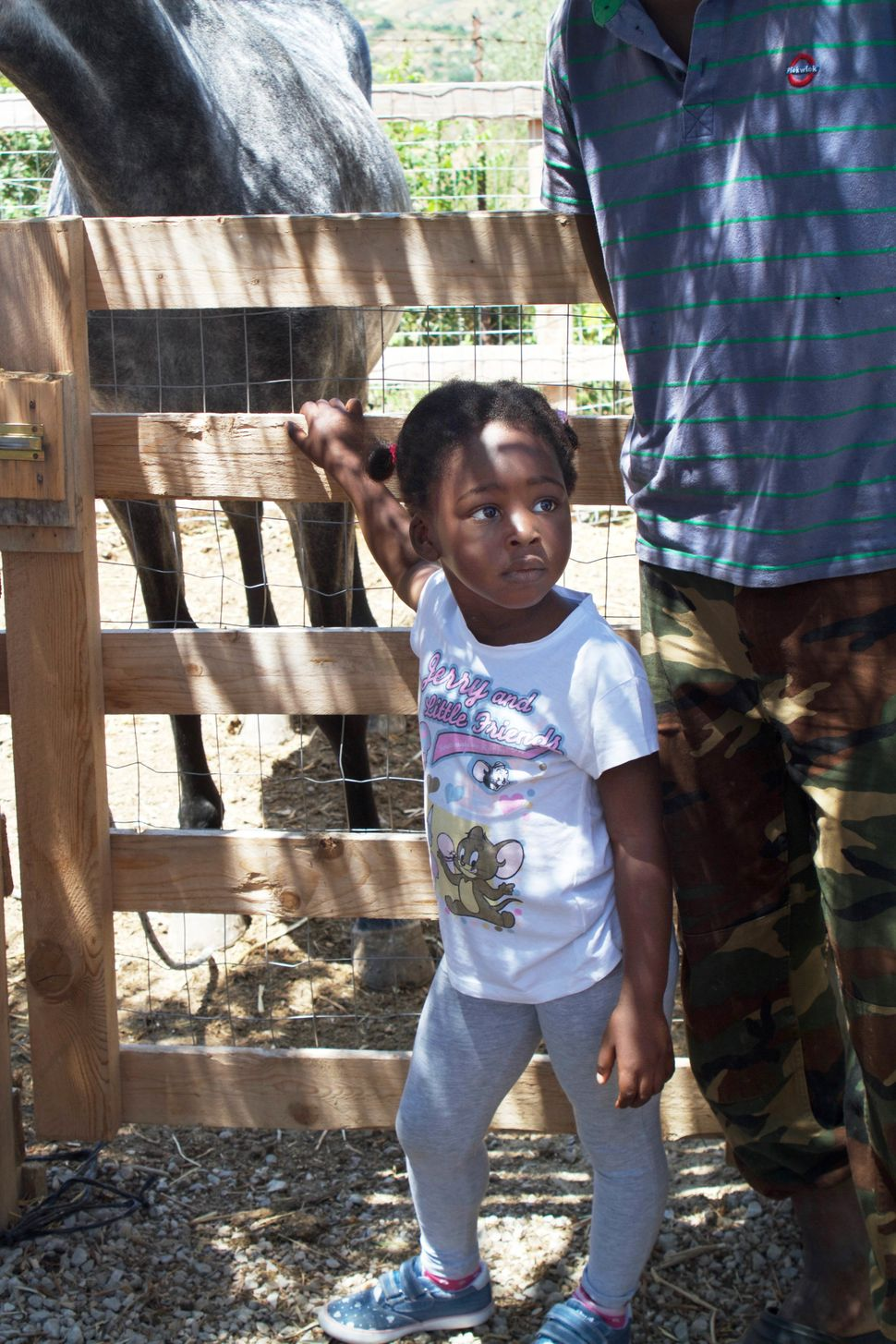 Prospery Sesay, 3, hangs out on the farm while her dad sells produce he picked in the Palermo market.