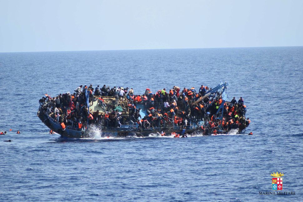 Refugees and migrants are seeing jumping from a capsizing boat in the middle of the Mediterranean on May 25, 2016.