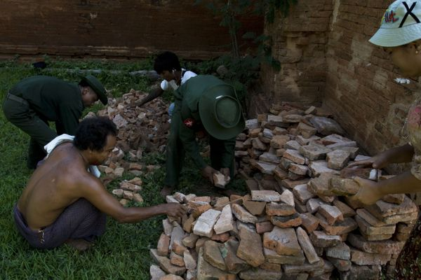 Myanmar military staff and a police officer collect the pieces of bricks of Dhammayangyi temple.