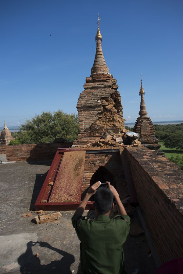 Myanmar military staff take pictures of the damage at the ancient Htilominlo Temple on August 25, 2016.