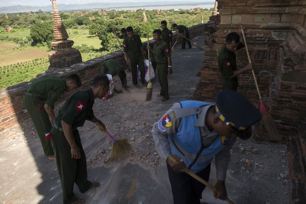 Myanmar military staff and a police officer collect the pieces of bricks at the damaged ancient Htilominlo Temple on August 2