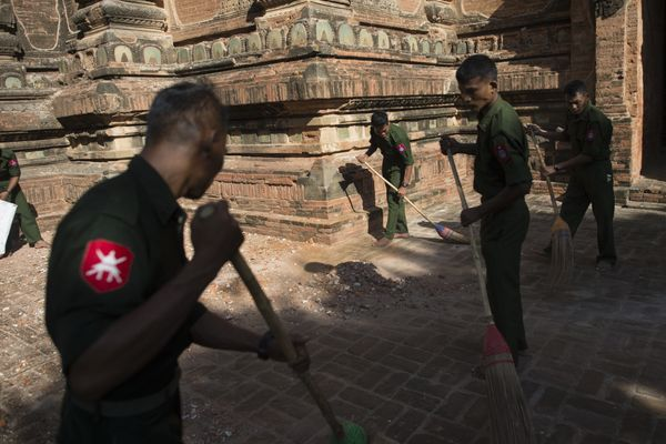 Myanmar military staff sweep up debris at the damaged ancient Htilominlo Temple on August 25, 2016.