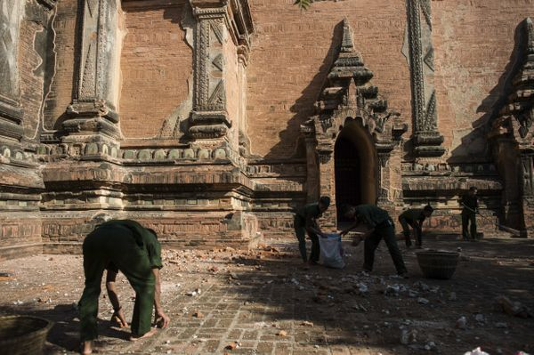 Myanmar military staff collect the pieces of bricks at the damaged ancient Htilominlo Temple on August 25, 2016, after a 6.8