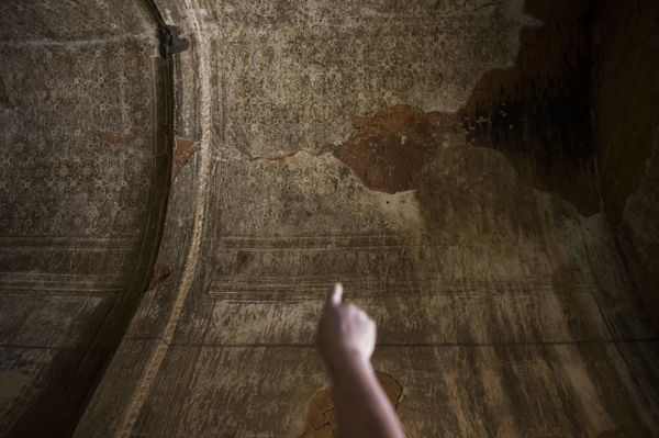 A man points to the ceiling where pieces of a mural painting have broken off at the damaged, ancient Htilominlo Temple on Aug