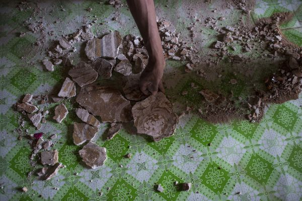 A man collect the pieces of mural painting scattered on the floor at the damaged, ancient Htilominlo Temple on August 25, 201