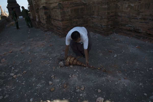 A officer collects a roof part at the damaged, ancient Htilominlo Temple on August 25, 2016, after a 6.8 magnitude earthquake