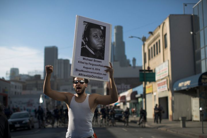 A protester holds a poster showing 18-year-old Michael Brown, who was killed by Ferguson police in 2014.