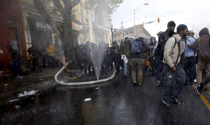 A fire hose cut by Baltimore protesters sprays water into the air as a line of police move toward a burning CVS dru