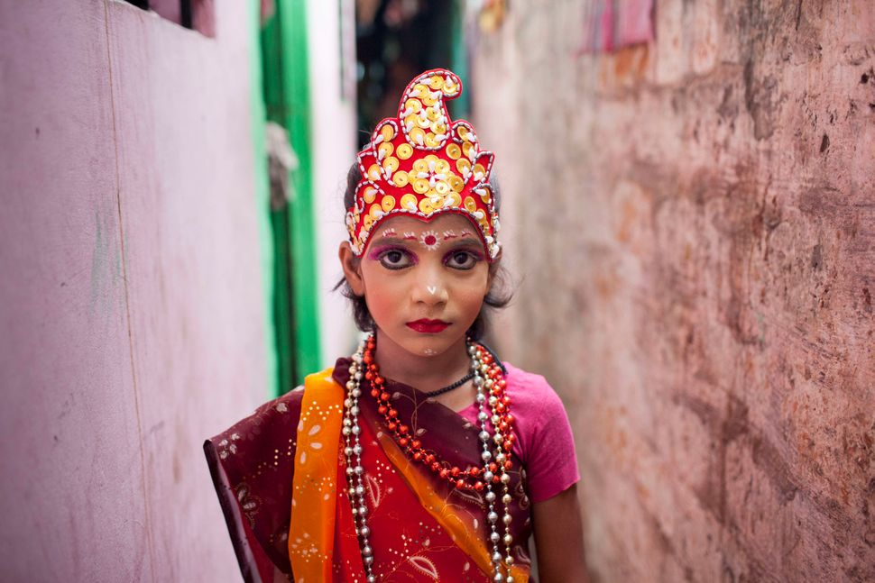 Agirl dressed like Radha, a Hindu goddess frequently depicted alongside Krishna, takes part in the celebration of Janma