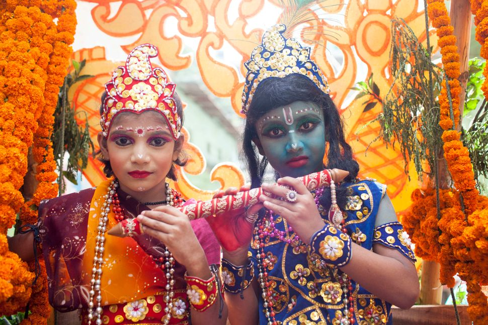 A boy and girl dressed like Lord Sri Krishna and Radha take part in the celebration of the religious festival Janmashtami.