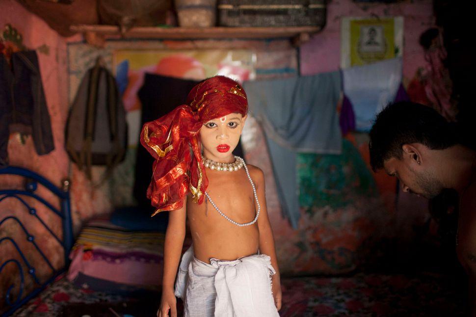 Aboy dressed like Lord Sri Krishna takes part in the celebration of the religious festival Janmashtami, marking the bir