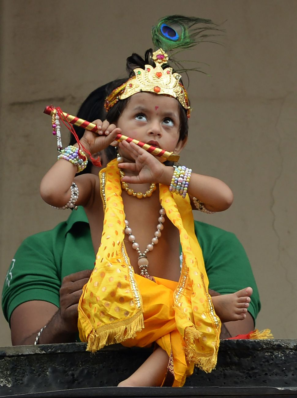 An Indian child dressed as Hindu god Lord Krishna looks on during the celebrations of Janmashtami in Mumbai on August 25, 201