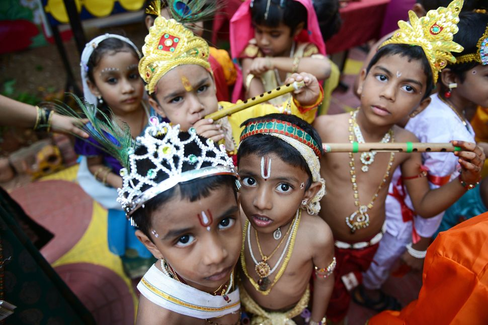 Indian children dressed as Hindu god Lord Krishna pose for a photograph at a fancy dress competition on the occasion of Janam