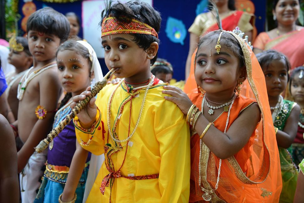 Indian children dressed as Hindu god Lord Krishna and his consort Radha pose at a fancy dress competition on the occasion of