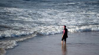 A Moroccan woman wearing a 'burkini', a full-body swimsuit designed for Muslim women, enters the sea at Oued Charrat beach, near the capital Rabat, on August 17, 2016. / AFP / FADEL SENNA        (Photo credit should read FADEL SENNA/AFP/Getty Images)