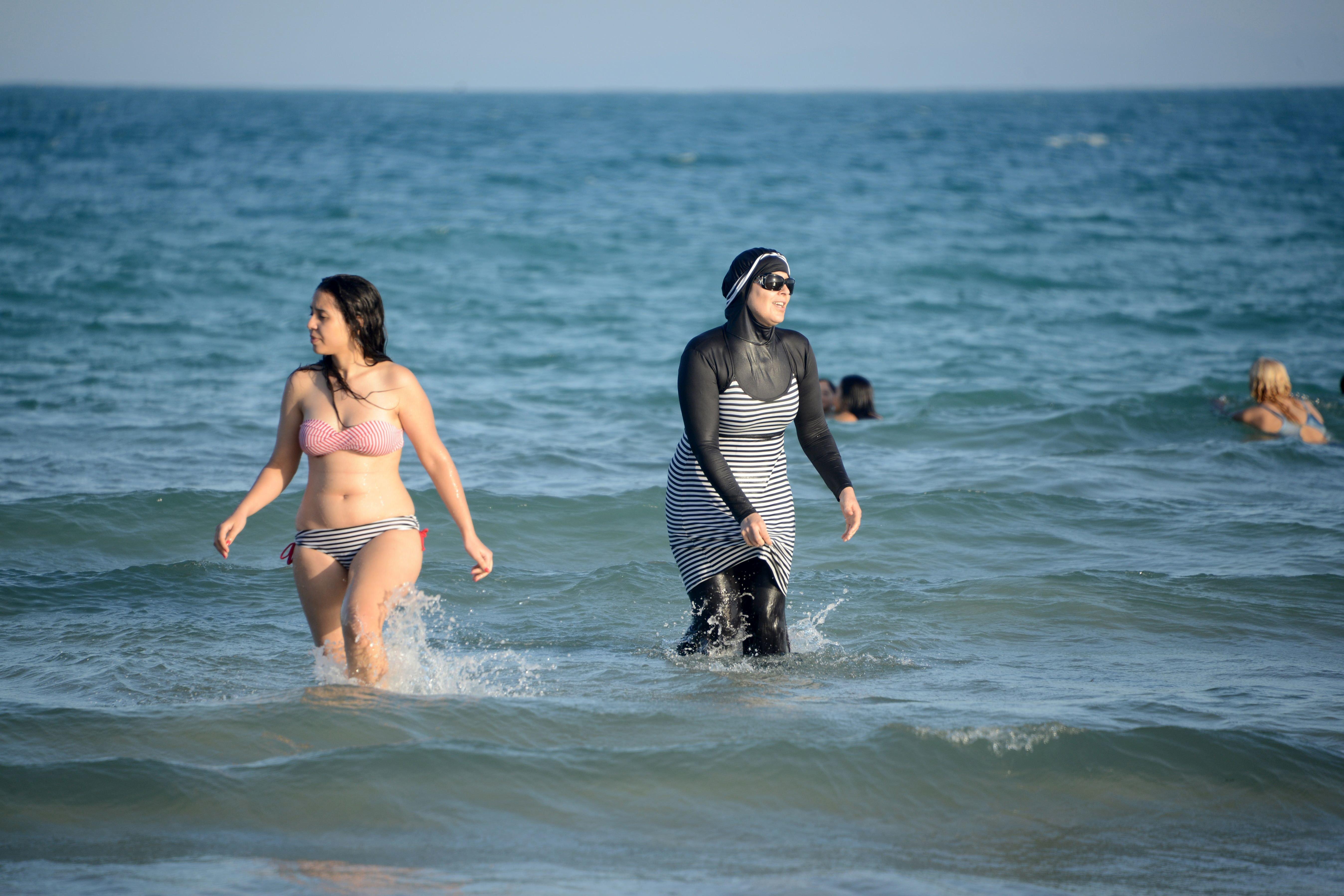 "Tunisian women, one wearing a ""burkini,"" a full-body swimsuit designed for Muslim women, swim on Aug. 16, 2016, at Ghar El Me"