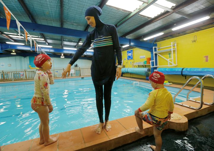 Australian swimming instructor Fadila Chafic wears her full-length 'burkini' swimsuit during a swimming lesson with her child