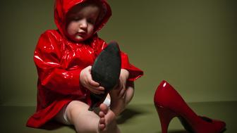 Toddler putting on adult high-heeled shoes