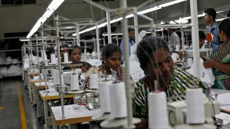 """Employees sew clothes at the Estee garment factory in Tirupur, in the southern Indian state of Tamil Nadu June 19, 2013. With knitwear exports of over $2 billion a year, India's garment manufacturing hub Tirupur has earned the nickname """"Dollar City,"""" but its allure for price-conscious global retailers obsessed by discounts of as little as one U.S. cent pales before Bangladesh. Picture taken June 19, 2013. REUTERS/Mansi Thapliyal (INDIA - Tags: BUSINESS EMPLOYMENT TEXTILE)"""